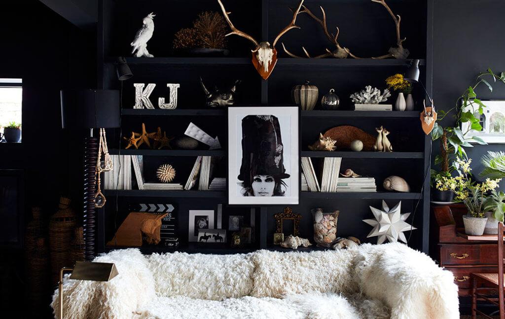 vintage coral, skulls and ornaments on black shelves.