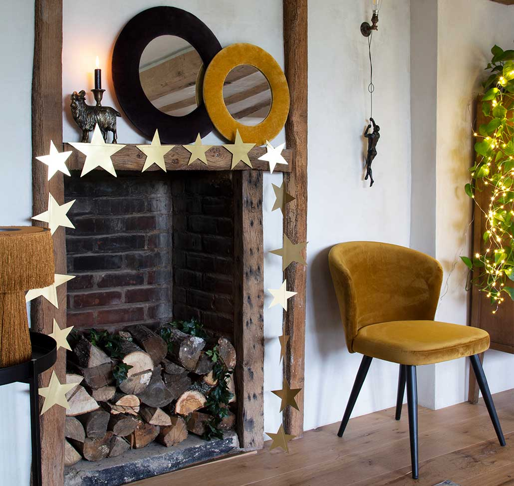 Mustard home decor for Christmas ideas with gold chair and star garland over fireplace