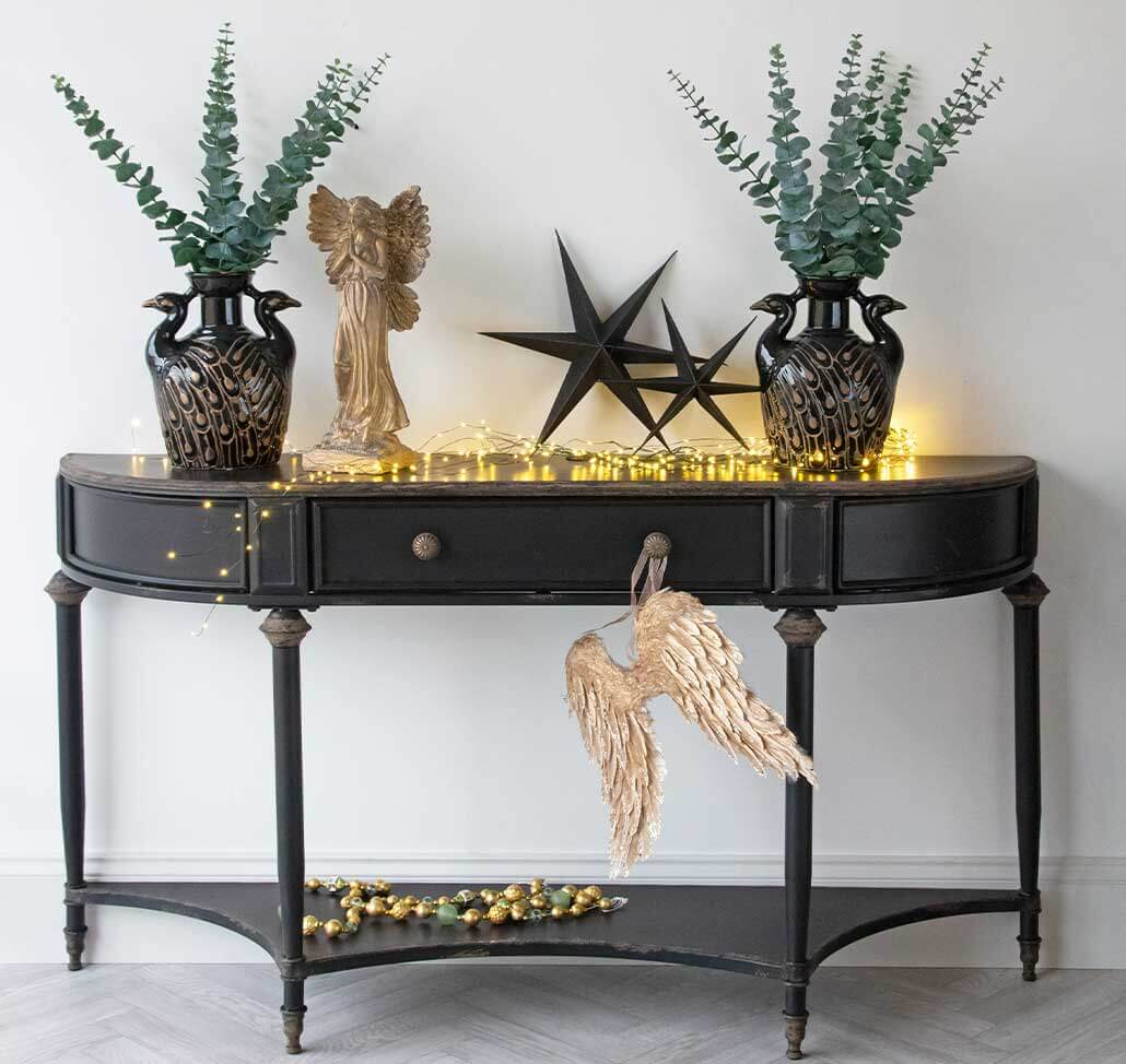Christmas decor ideas for the entrance hallway black sideboard with fairy lights and black stars