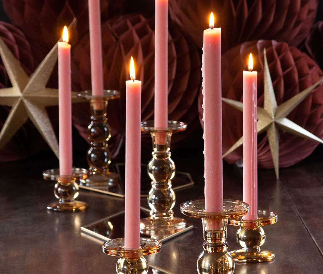 Lifestyle image of pink dinner candles in amber candlestick holder.