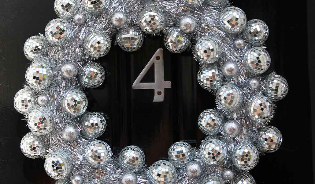 Lifestyle image of silver disco ball christmas wreath on black door.