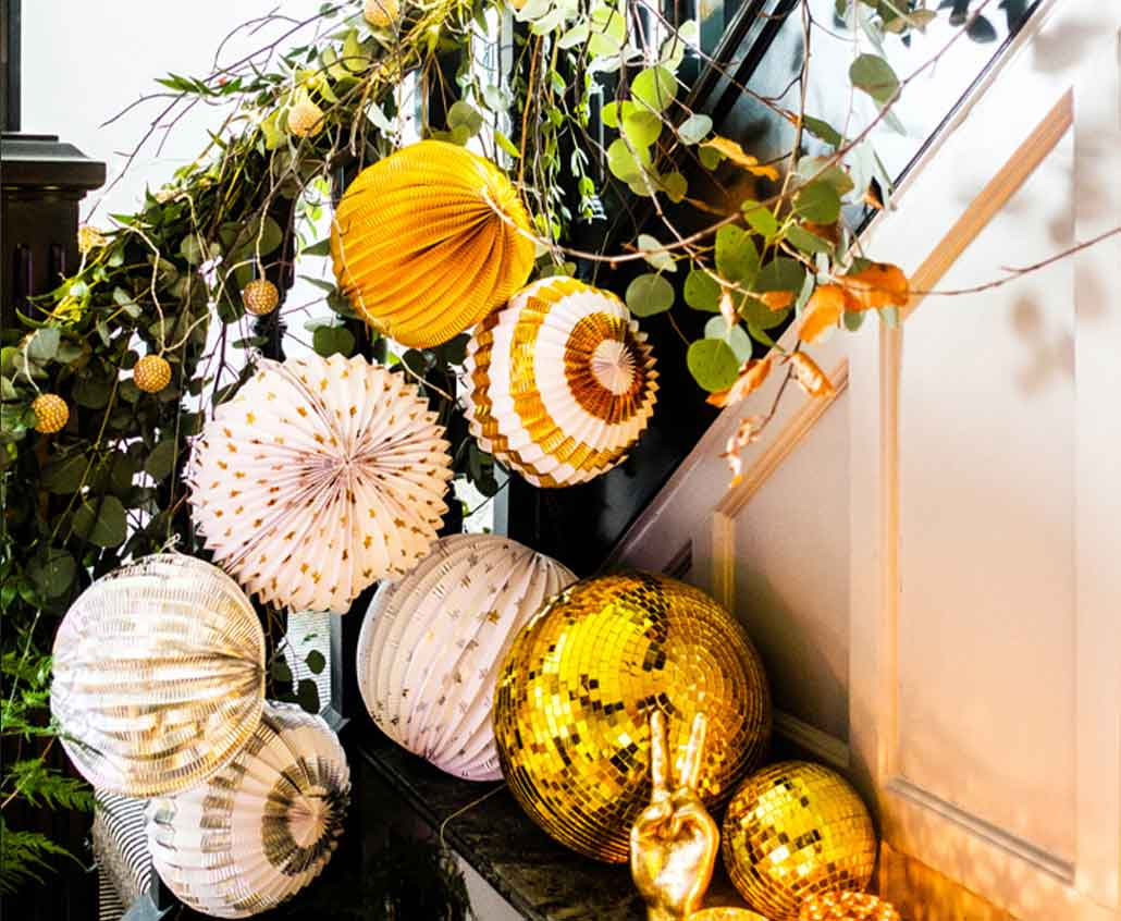 Lifestyle image of decorated staircase with ivy, globe paper balls, disco balls and a gold peace hand.