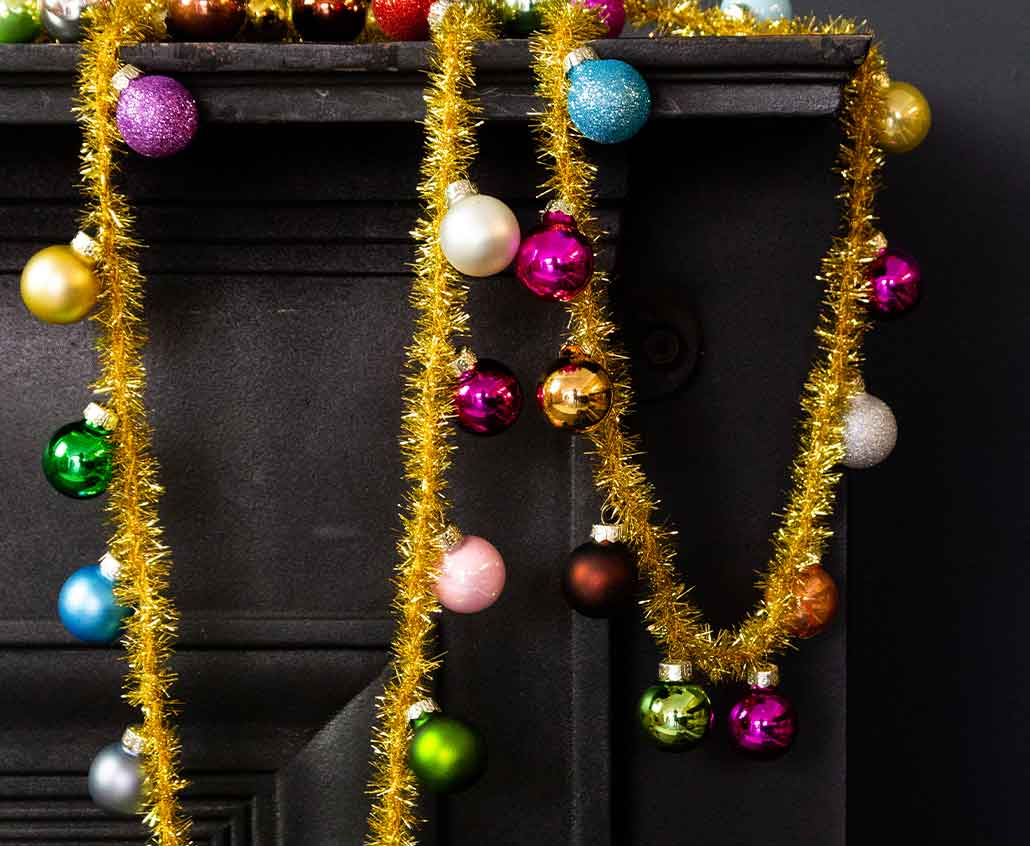 Image: Black fireplace with gold tinsel and colourful baubles draped over the edge.