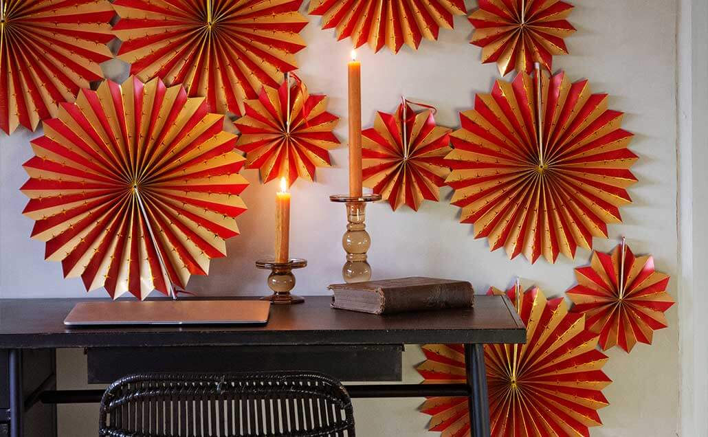 Image of wall decorated with colourful paper pinwheel decorations.