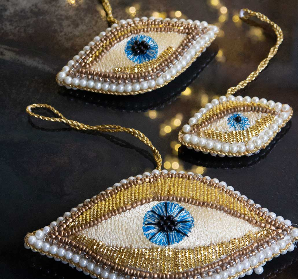 Lifestyle image of three golden beaded eye decorations with blue pupil.