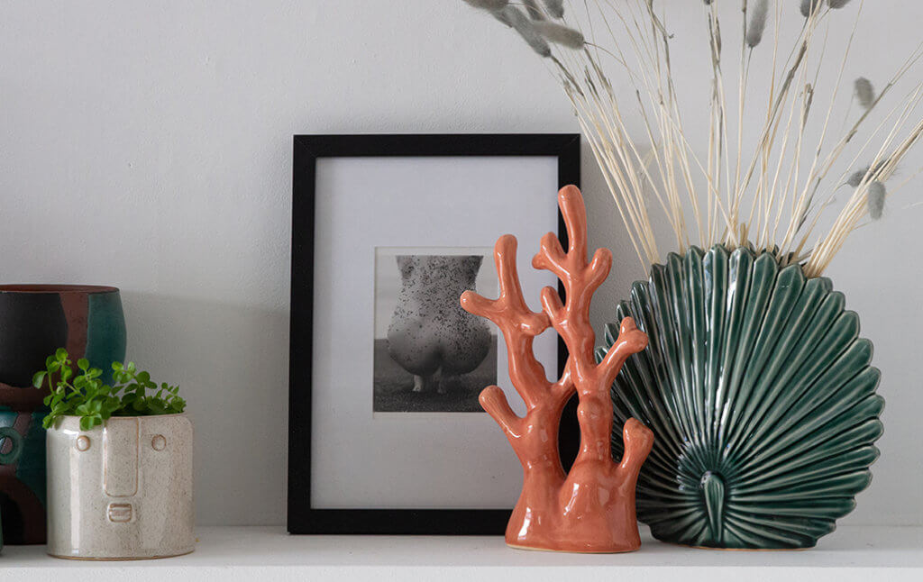 a selection of coral ornaments, vases and frames styled in odd numbers