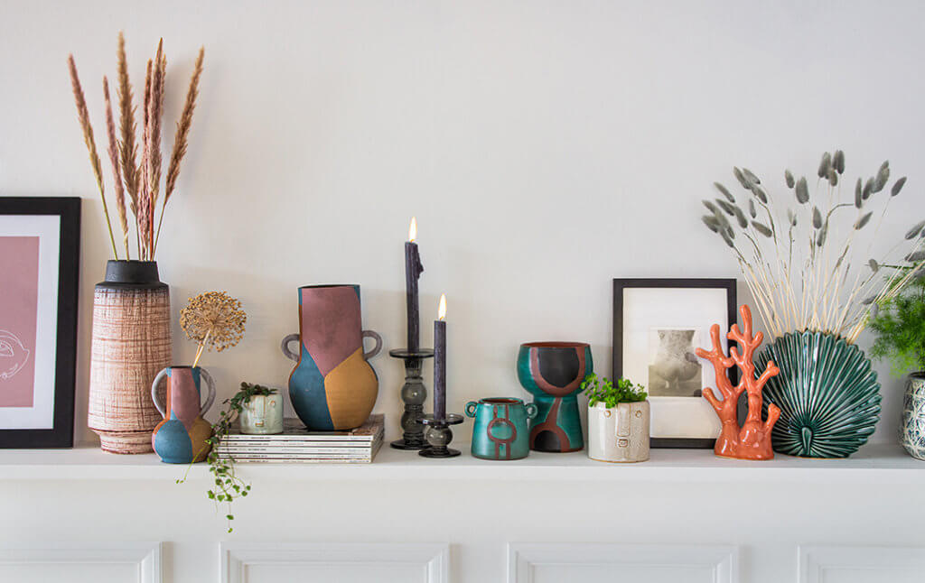 a shelf with display vases, pots, florals and quirky objects