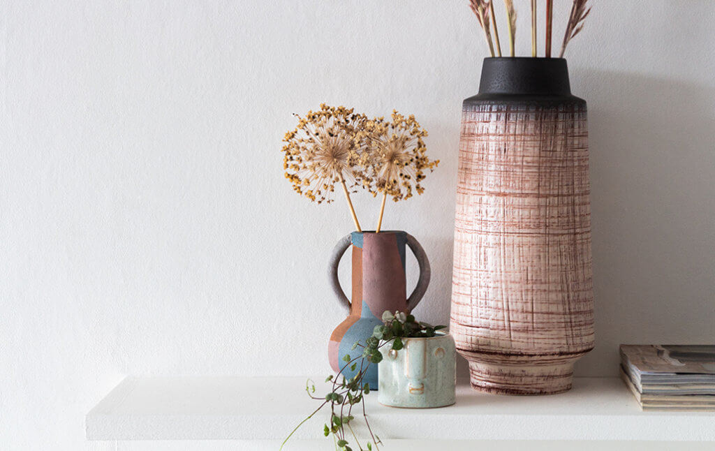 textured plants in vases on shelf